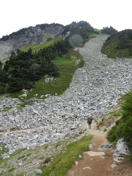 Hikers crossing the talus slope on the way to Cascade Pass.