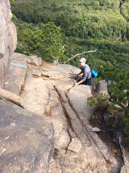 Using the iron rungs to get up to the next level on the Beehive Trail.