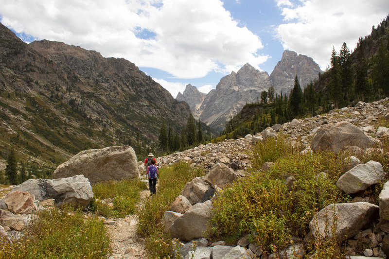 Hiker descending Upper Cascade Canyon with Grand Teton in the background.