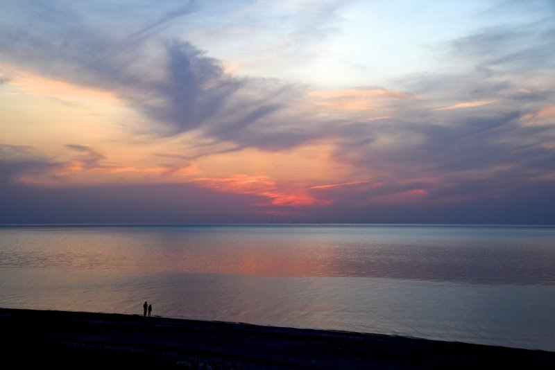 A couple enjoying the incredible colors of the Lake Michigan sunset.