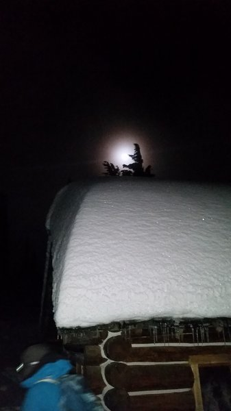 A full moon peeps out over a lean-to on an evening hike to Mt. Kit Carson.