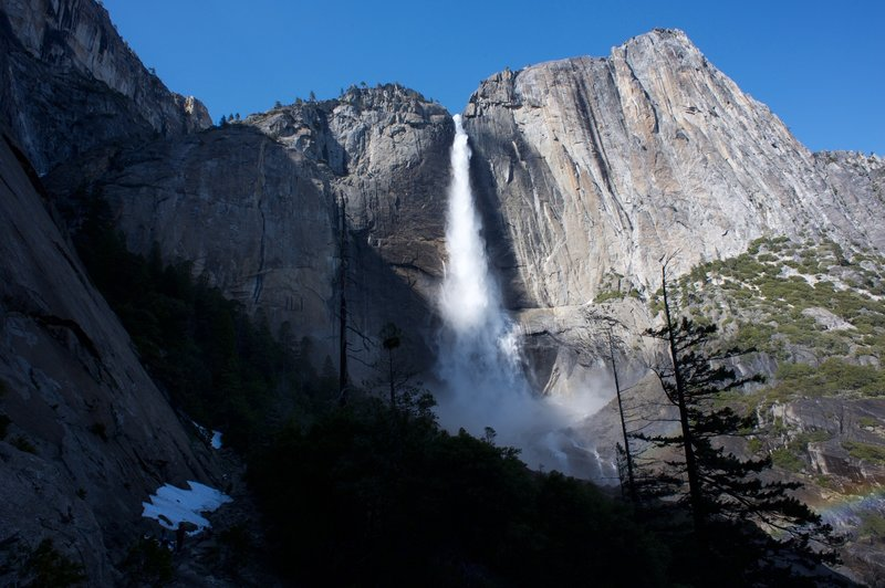 The trail hugs the rock wall on the left as Upper Yosemite Falls shines in the late noon sunlight.  When the spring snowmelt happens, the falls run at full force.