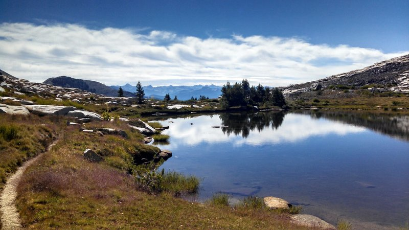 Small alpine lake along Isberg Trail with the Silver Divide and John Muir Wilderness high country in the distance.