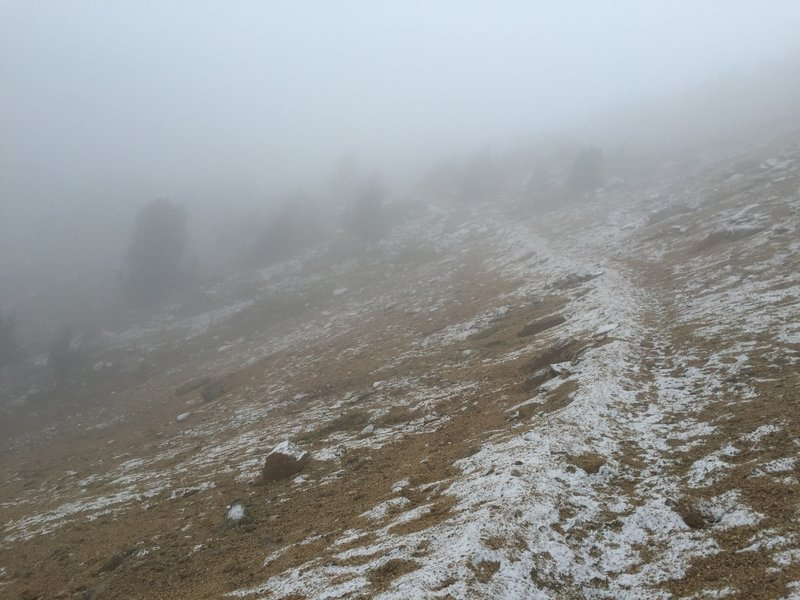 Fog drifts over the trail approaching Cathedral Pass.