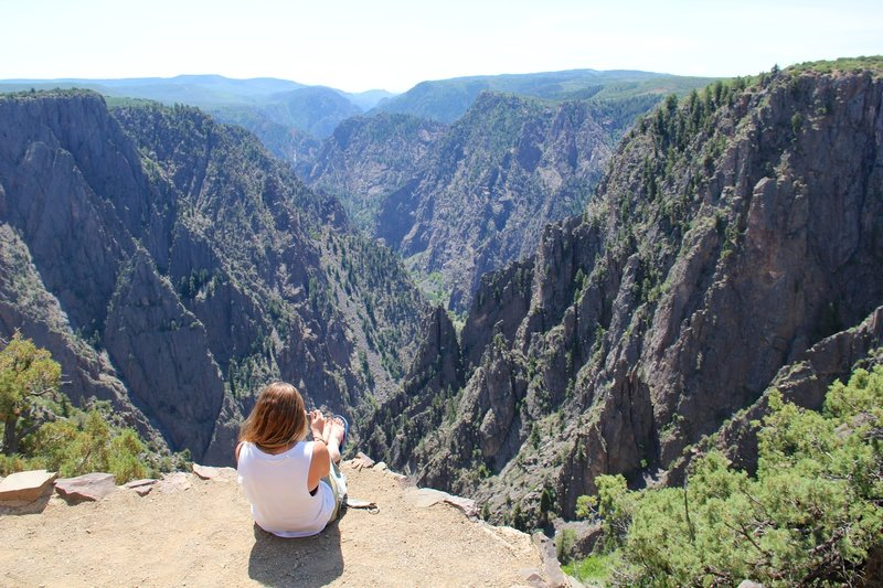 A woman relaxes at the first overlook on the Rim Rock Trail.
