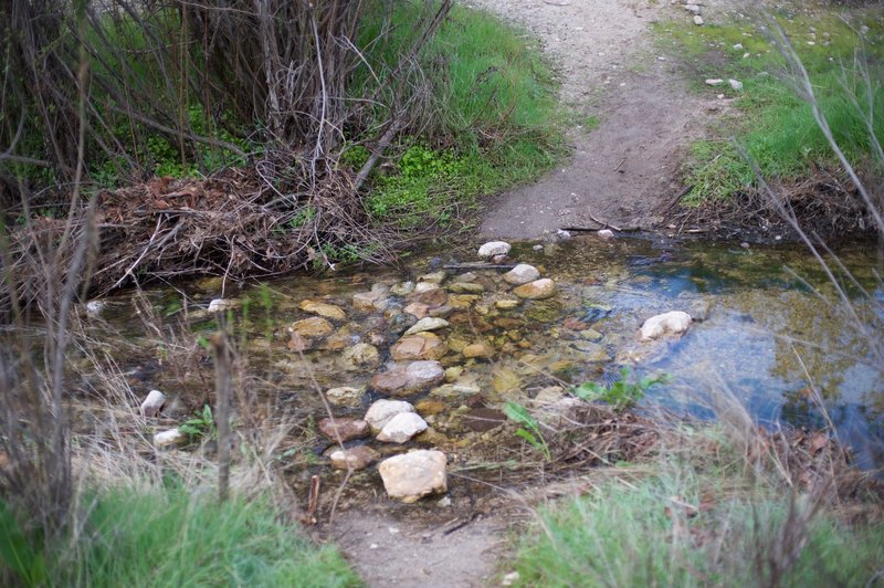 The creek crossing in the winter when water is running downstream.