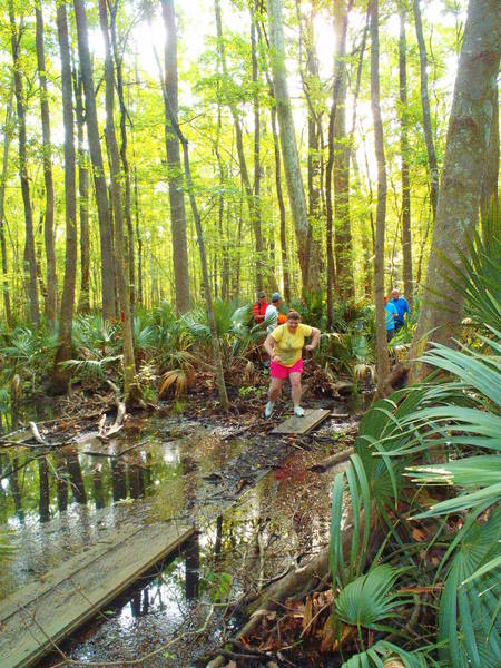 Runners crossing the wet section of the trail.