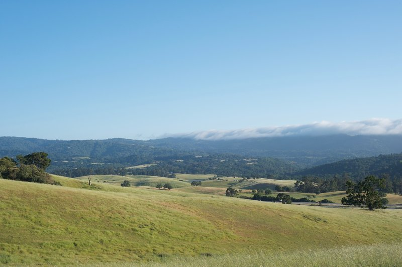 View from the trail of the surrounding hills as fog rolls in late in the day.