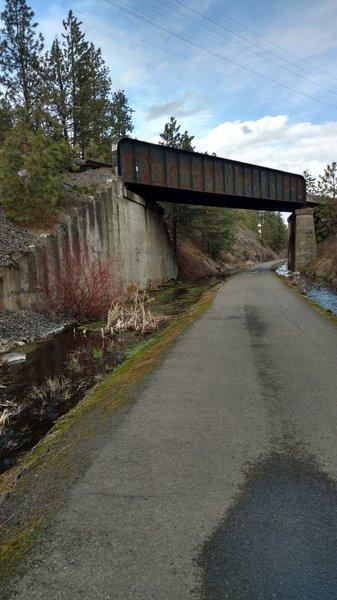 Railroad tracks cross over the trail, stream runs alongside.