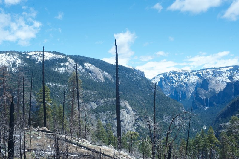 The view toward Yosemite Valley. El Capitan peeks above the ridge line, and Bridalveil Falls can be seen on right hand side.