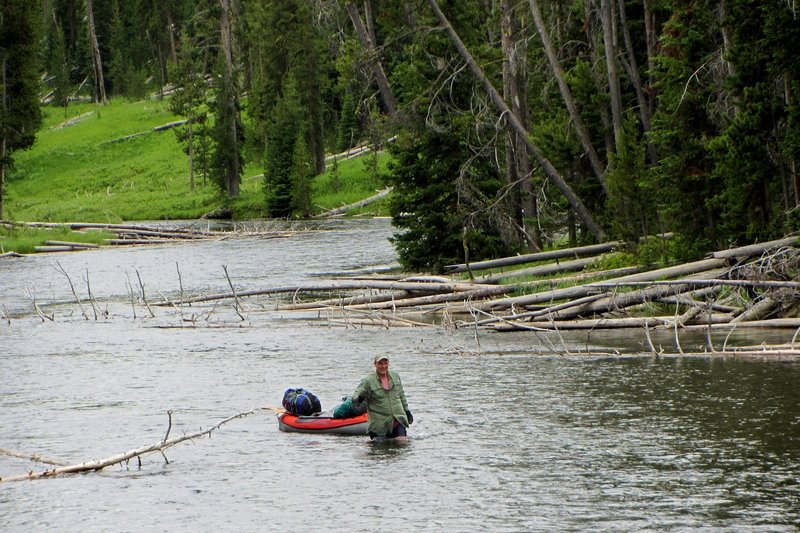 A kayaker walks his kayak up the Lewis River Channel through a section that flows too fast to paddle against.