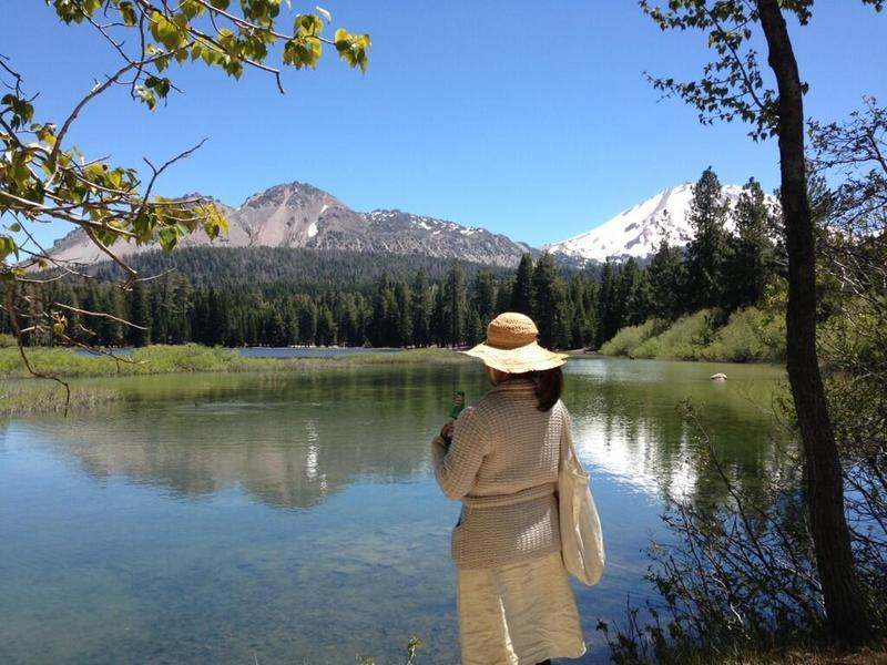 A woman enjoys a snack along the southern portion of the Manzanita Lake Loop Trail. Chaos Crags (right) and Lassen Peak (left) rise above.