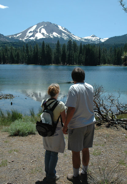 A couple enjoys a view of Lassen Peak from the southern shore of Manzanita Lake.