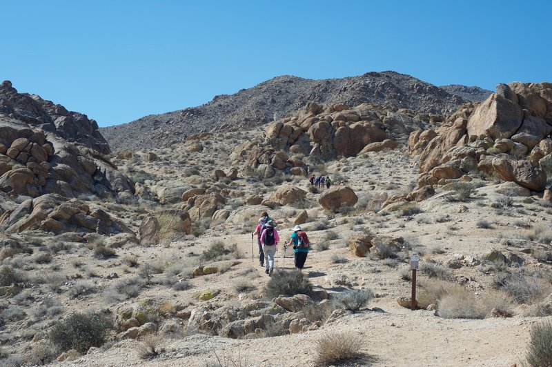 The hike starts climbing immediately past large boulders on both sides of the trail.