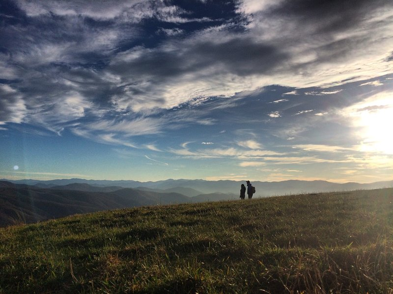 The Peoples Trail - A photo shot of a couple along the Appalachian Trail from atop Max Patch Mountain in Pisgah National Forest. There are many stunning views along the 2,200-mile east coast trail, but nothing quite like the panoramic scene of the Blue Ridge Mountains.