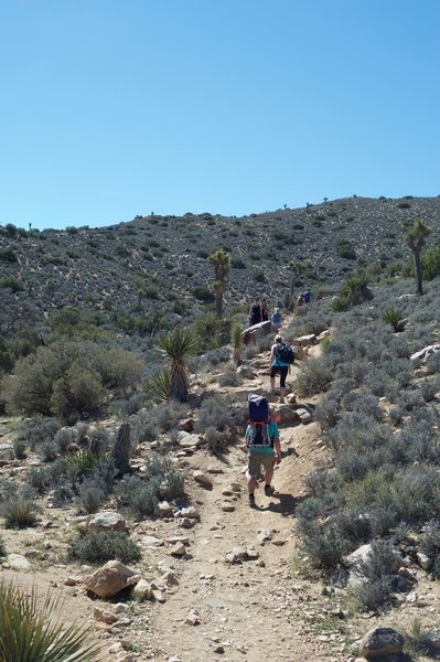 Hikers pass through the saddle and continue the ascent to the summit of the mountain.