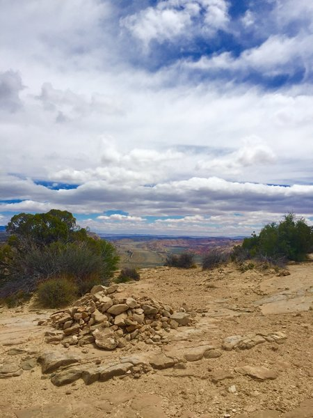 A large rock pile marks the end of the trail at the top of the sandstone cliff viewpoint. The viewpoint spans a few hundred feet in both directions displaying the valley below and mountain ranges in the distance.