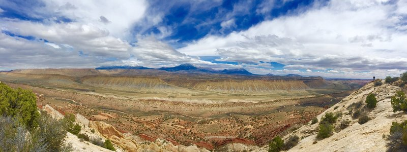 Panoramic view of the valley below and the Henry Mountains in the distance.