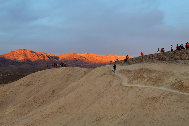 The mountains glow orange in the sunset near Zabriskie Point.