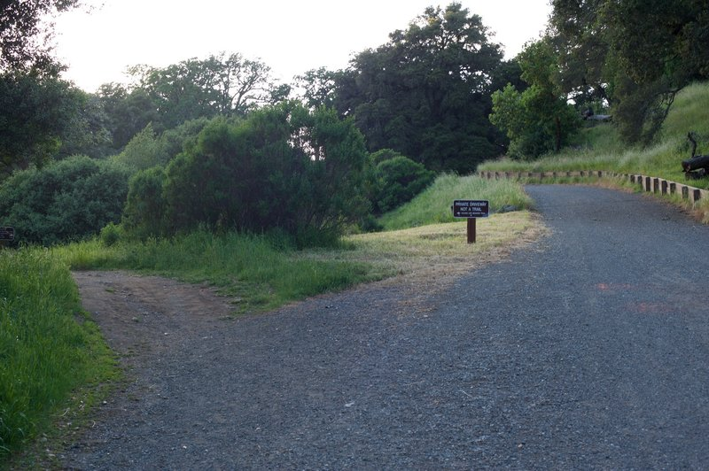 The Meadow Trail cuts off to the right as the private drive continues straight ahead.