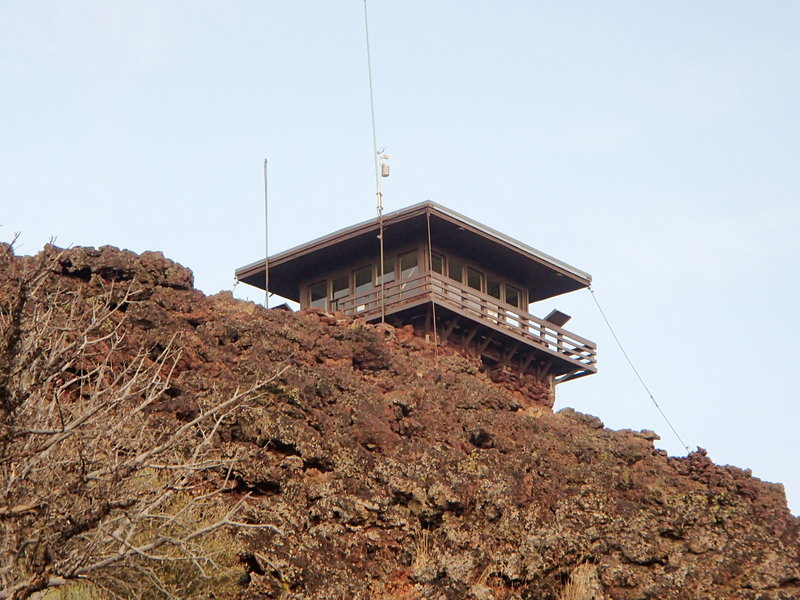 The fire lookout sits at the summit atop lava splatters.