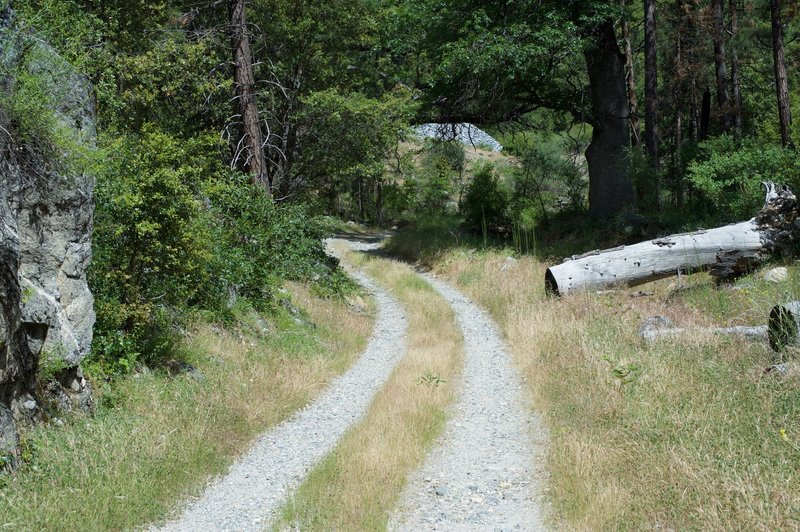 The trail becomes a two gravel tire tracks after the bridge.
