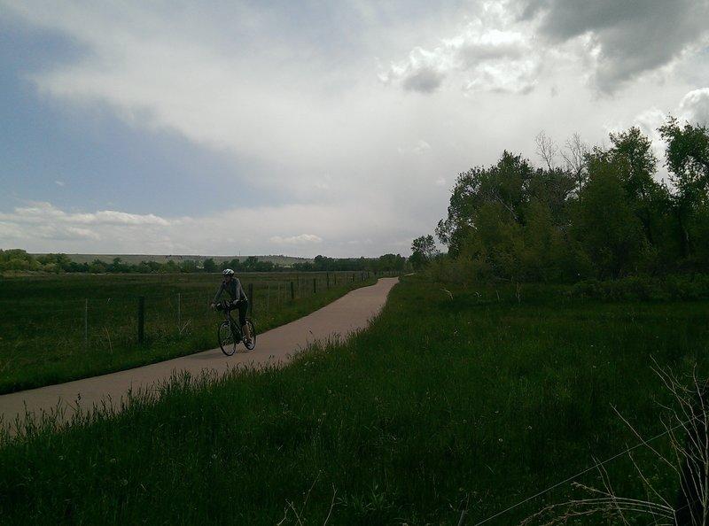 A biker along the paved South Boulder Creek Trail.