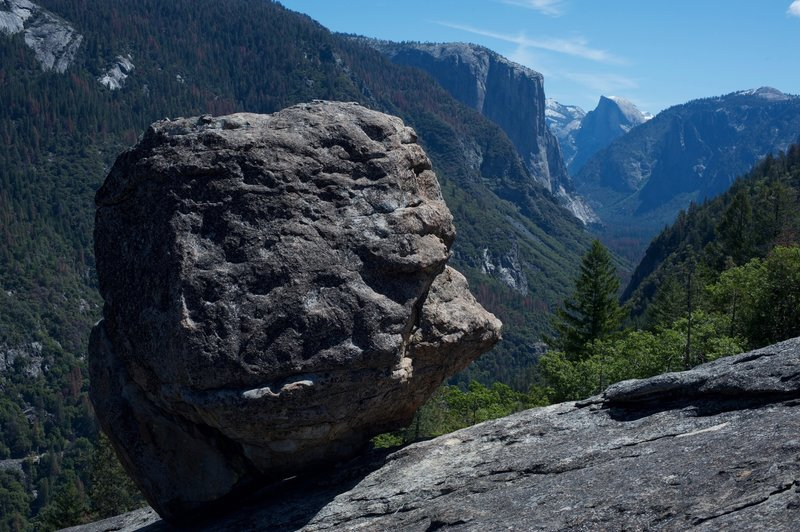 A glacial erratic with El Capitan and Half Dome in the background.