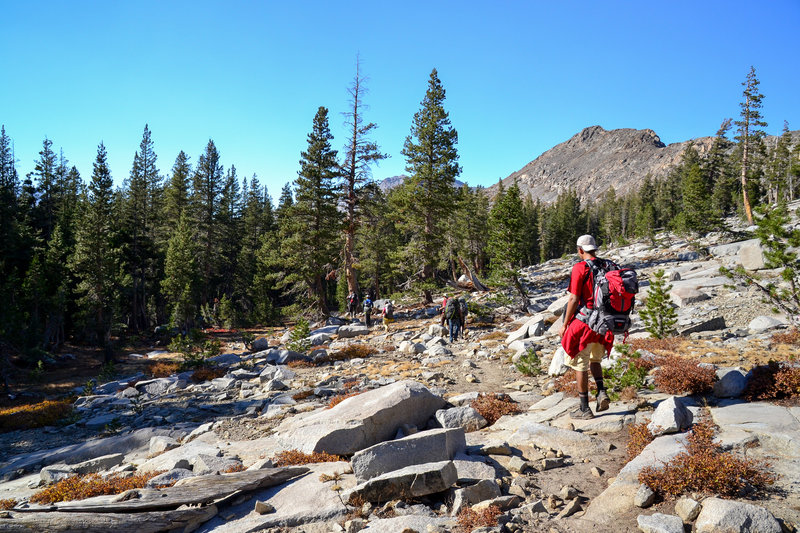Hikers picking their way through a small boulder field along the PCT.