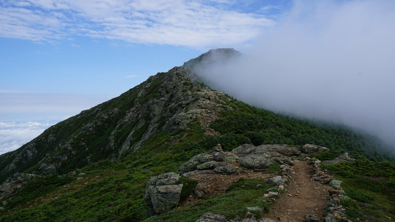 The summit of Mt. Lafayette looms out of the clouds ahead.