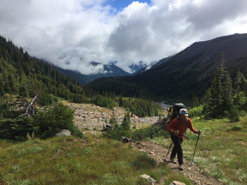A climber ascends above Glacier Basin towards the Inter Glacier on a primitive climbers trail.