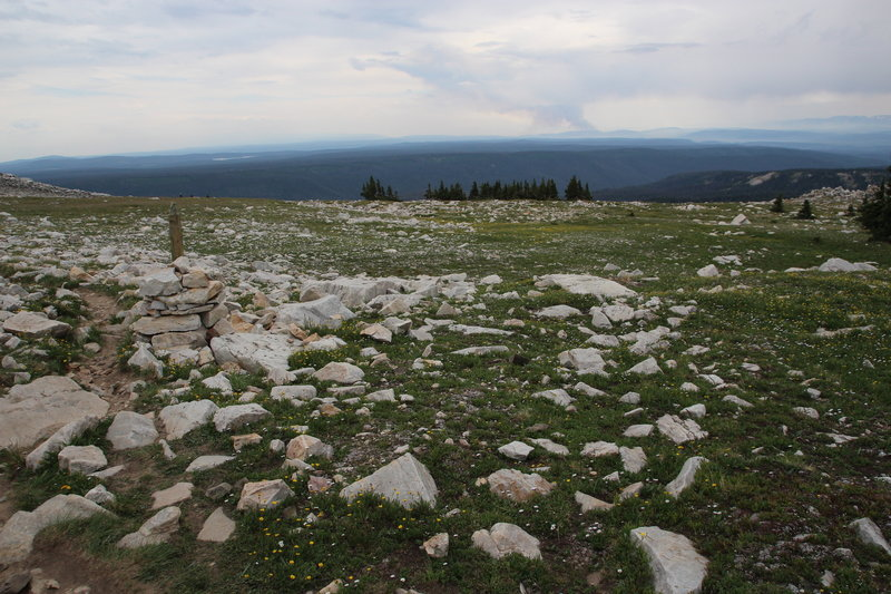 Rock piles with wooden posts mark the trail. The Beaver Creek Fire can be seen in the distance burning in northern Colorado.