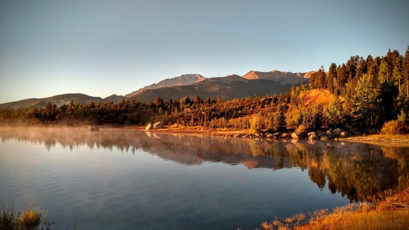Pike's Peak reflects off of the placid water in the early morning light.