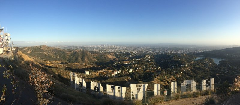 Standing above the Hollywood Sign with the city in the background.