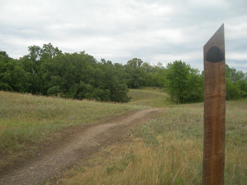 The gravel trail tread along with the angle-topped wooden marker post.