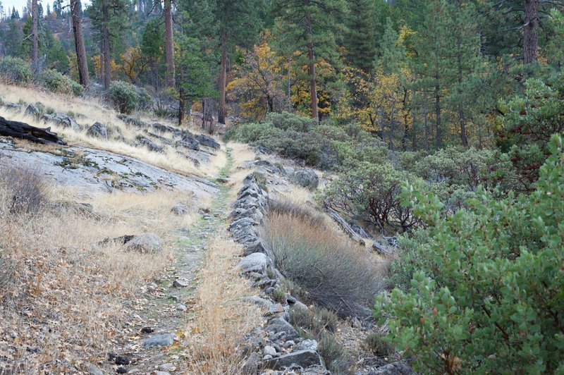 The trail skits along a rock barrier as it makes its way through an open area.