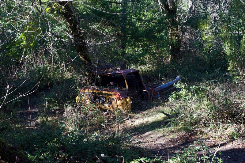 An old, abandoned truck sits off to the side of the trail.