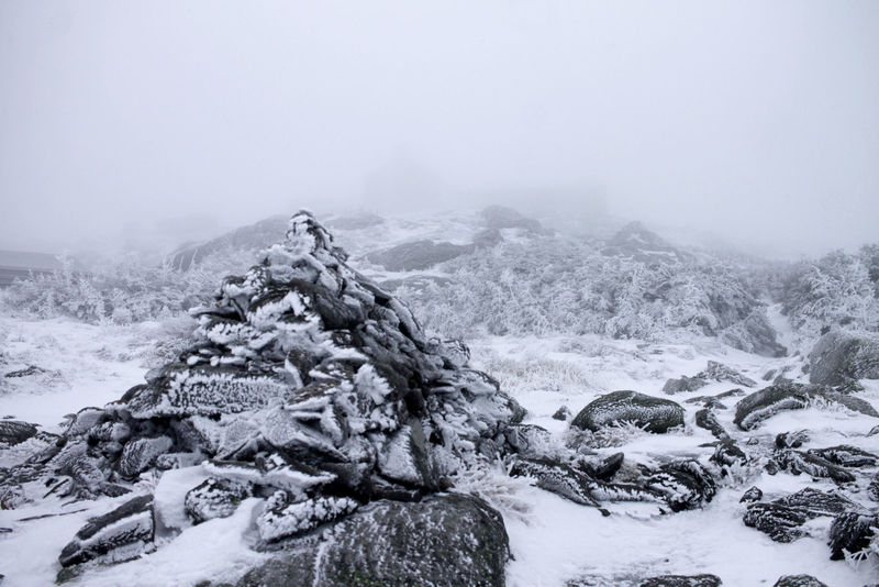 With 50 ft visibility, you can just barely make out the outline of Lakes of the Clouds hut in the background behind the cairn.