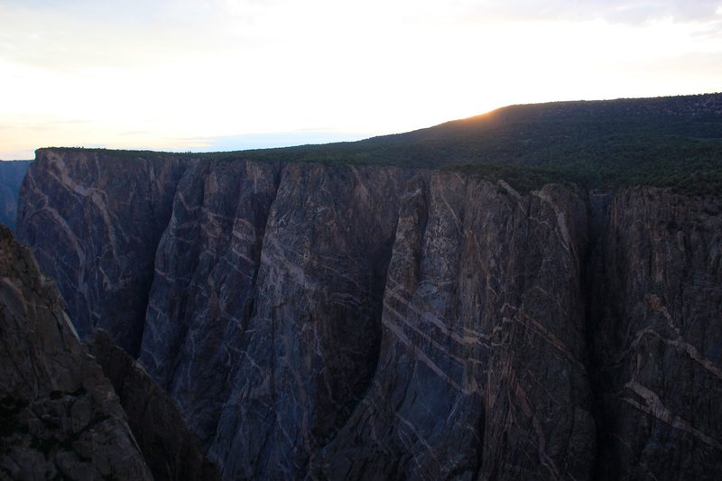 While the sun hides behind the cliff, the precambrian rocks shine.