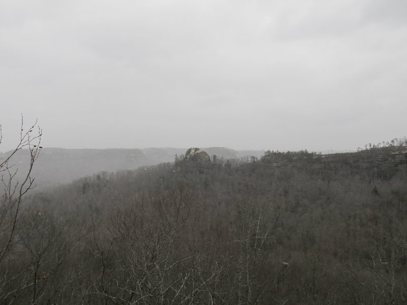 Courthouse Rock looms from the top of Double Arch in some windy snow flurries.