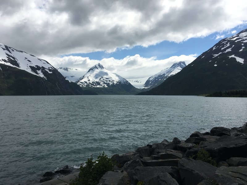 Snow-capped mountains see the sun peek through the clouds in the middle of summer on the Kenai Peninsula.
