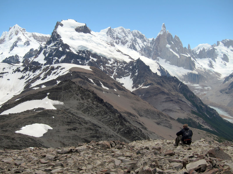 An adventurer enjoys the view from the summit of Loma del Pliegue Tumbado.