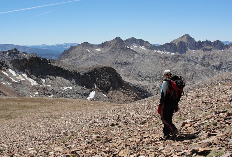 A hiker descends to McGee Pass from Red Slate Mountain.