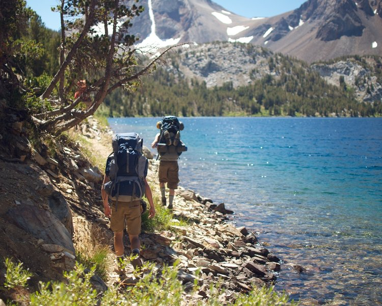 A pair of hikers navigates the spectacular shoreline of Lake Dorothy on the Bighorn Lake Trail.
