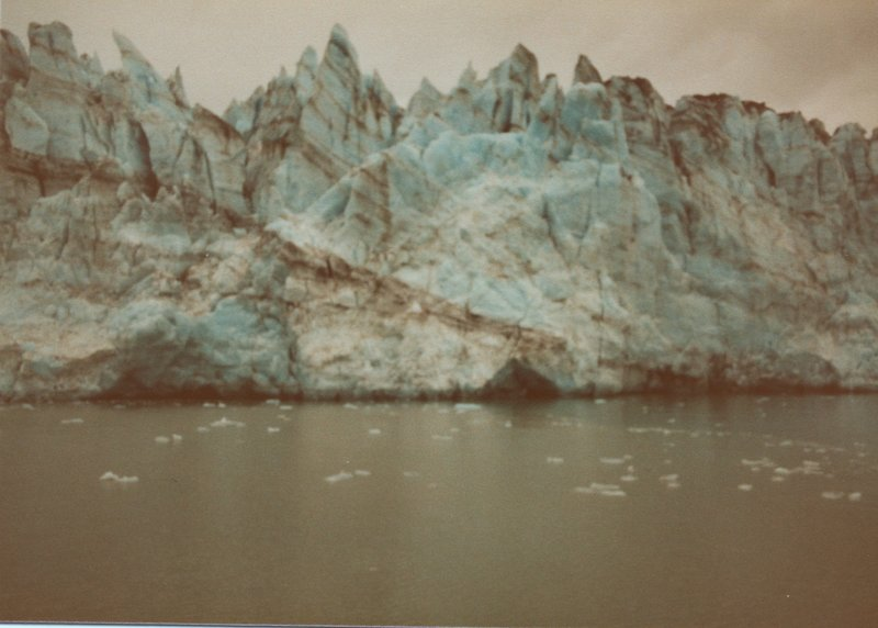 Marjerie Glacier poses with tiny remnants of calved icebergs floating in front of it.