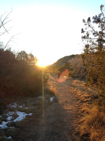 A woman and her dog head west from Bridal Veil Falls chasing the sunset.