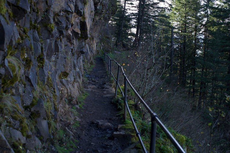 The trail follows the rock face of the cliff as it makes its way toward the falls. This is looking back down the trail.