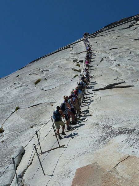 The infamous cable climb on Yosemite's Half Dome rewards visitors with stunning views from the top.