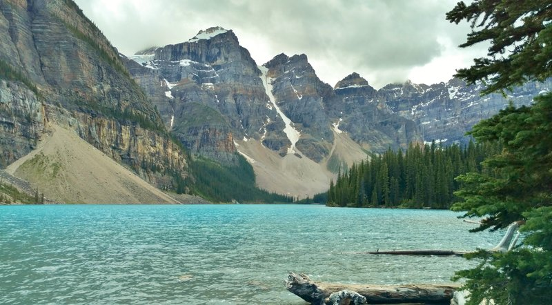 Moraine Lake is nestled within the Valley of Ten Peaks. Left-to-right is the base of the Tower of Babel, Mt. Babel, Mt. Fay, Tonsa Peak, and Mt. Allen (in a cloud).