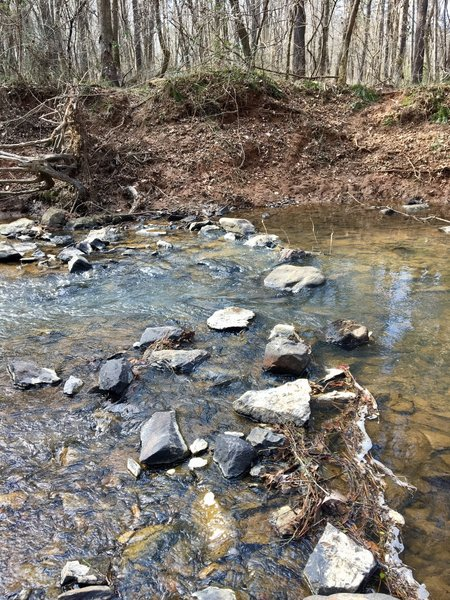 Take care in placing your feet as you navigate this creek crossing along the trail.